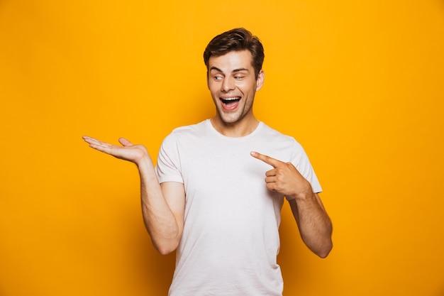 Портрет счастливого молодого человека, указывая пальцами