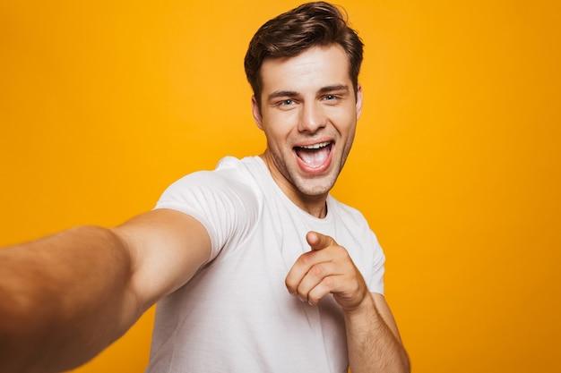 Портрет счастливого молодого человека, делающего селфи