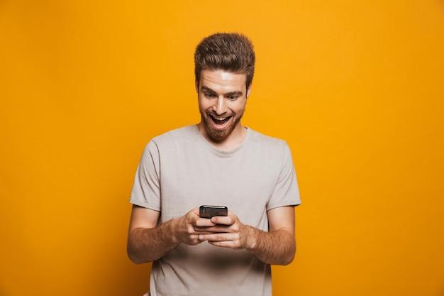 Портрет счастливого молодого человека с помощью мобильного телефона