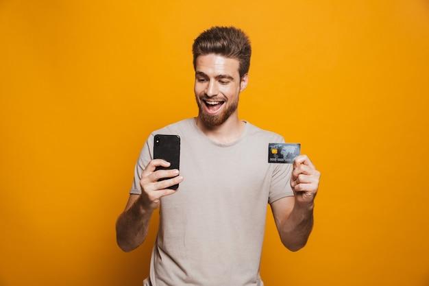 携帯電話を使用して幸せな若い男の肖像画