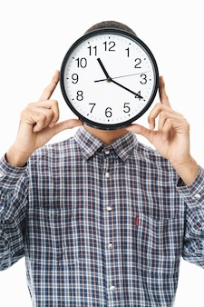 白の上に立っている格子縞のシャツを着て、壁時計で顔を覆う幸せな若い男の肖像画