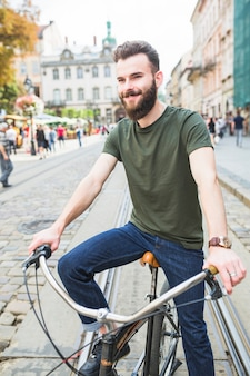 Portrait of a happy young man with bicycle