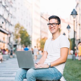Portrait of a happy young man with laptop