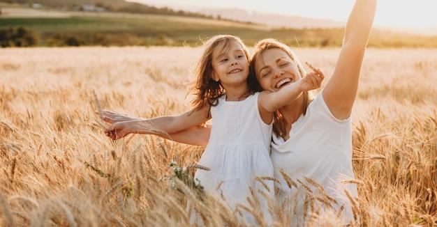 행복 한 젊은 어머니와 그녀의 사랑스러운 딸 연주와 밀의 분야에서 웃 고의 초상화. 자유 개념.