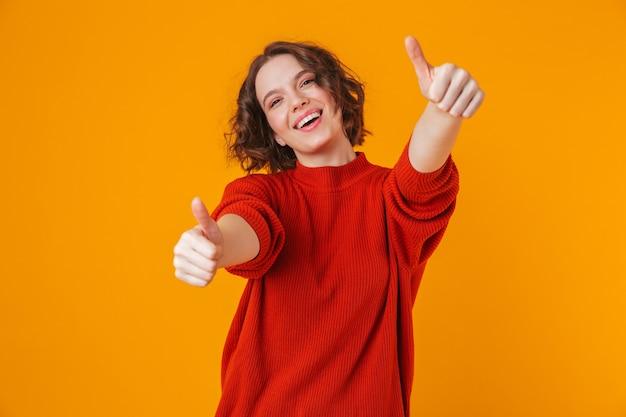 親指を立てて黄色の壁に孤立してポーズをとって幸せな若いきれいな女性の肖像画。