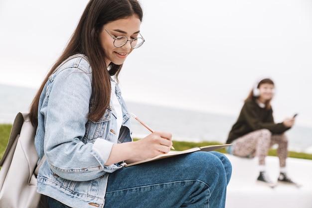 Портрет счастливого молодого симпатичного студента женщины нося очки сидя на открытом воздухе отдыхая написание заметок.