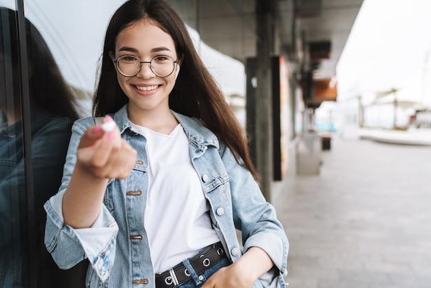 Портрет студента счастливой молодой красивой женщины в очках, идущих на открытом воздухе, отдыхая, слушая музыку с наушниками, дает вам один наушник.
