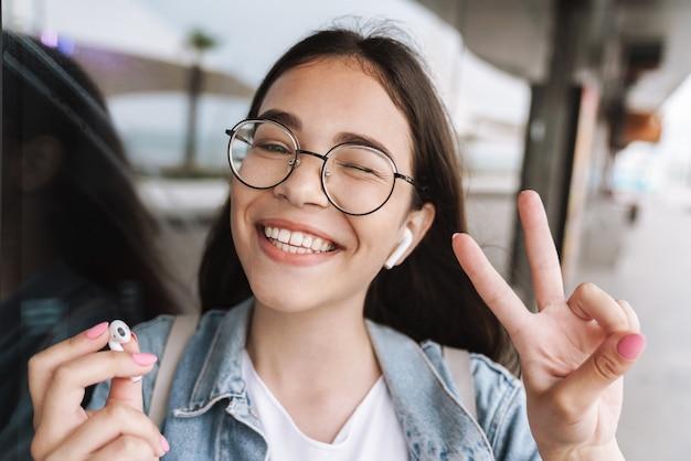 Портрет счастливой молодой красивой женщины-студента в очках гуляет на открытом воздухе, отдыхая, слушая музыку с наушниками, показывая жест мира