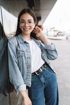 Портрет студента счастливой молодой красивой женщины в очках, идя на открытом воздухе, отдыхая, слушая музыку с наушниками.