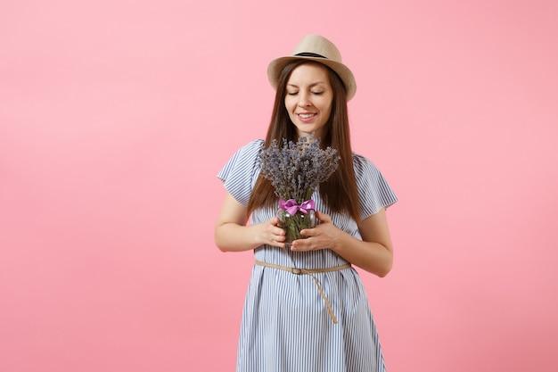 青いドレス、明るいトレンドのピンクの背景に分離された美しい紫色のラベンダーの花の花束を保持している帽子の幸せな若い優しい女性の肖像画。国際女性の日の休日の概念。