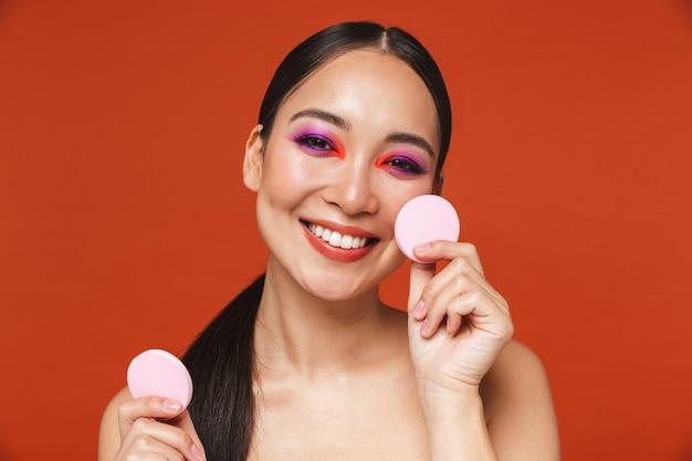Портрет счастливой молодой топлес азиатской женщины с волосами брюнетки, носящей яркий макияж, стоящей изолированной на красном и держащей губки для макияжа