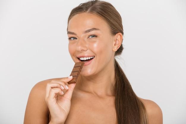 孤立したチョコレートの断片を食べる幸せな若いトップレスの女性の肖像画