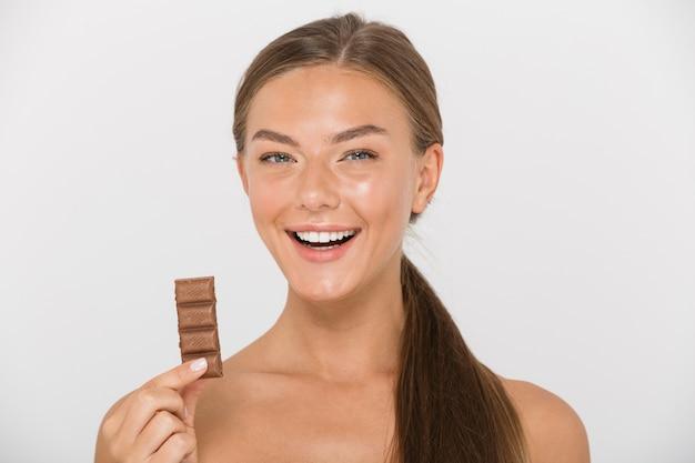 孤立したチョコレートの部分を保持している幸せな若いトップレスの女性の肖像画