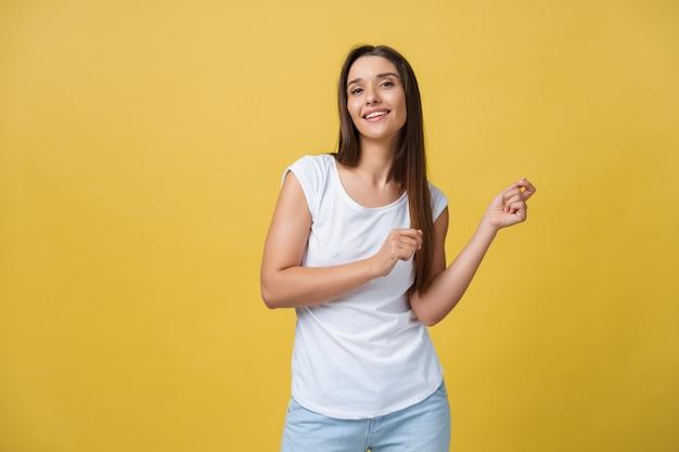 Портрет счастливой молодой женщины, танцующей на желтом фоне
