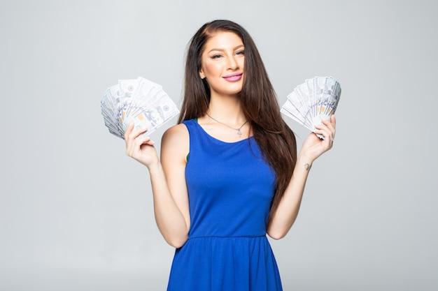 Портрет счастливой молодой женщины, одетой в платье, холдинг кучу денег банкнот, изолированных