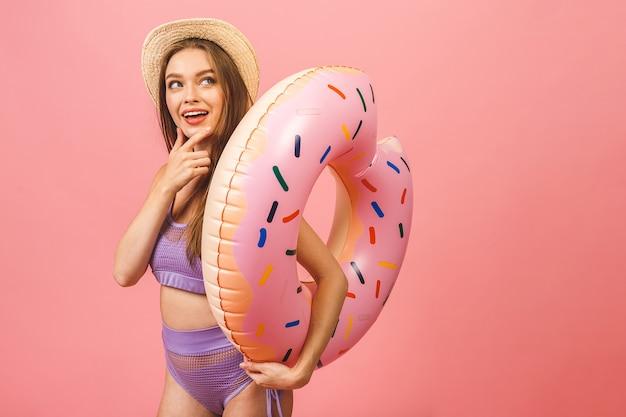 점프 하 고 수영 풍선 반지를 들고 수영복을 입은 행복 한 젊은 여자의 초상화