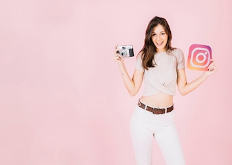 Portrait of a happy young woman holding camera and instagram icon