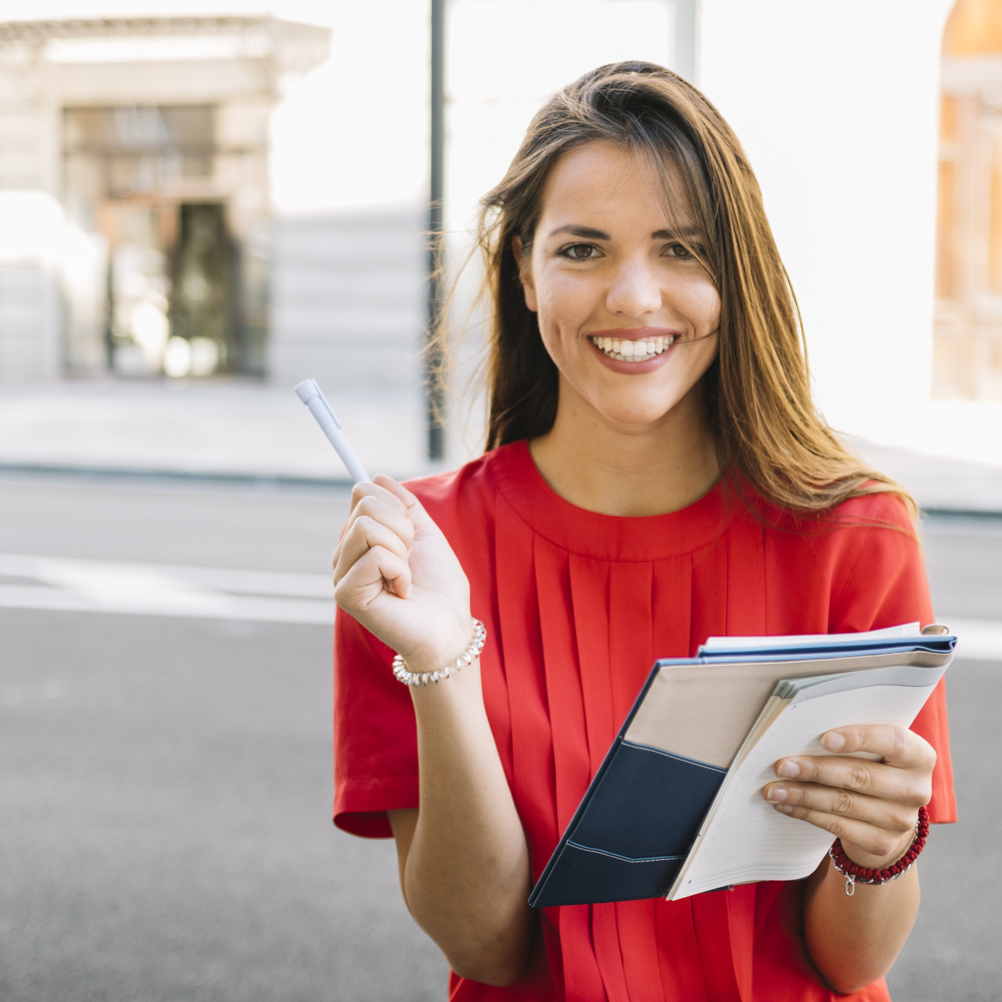 Portrait of a happy young woman holding diary