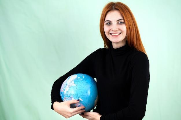 世界の地球儀を手に持った幸せな若い女の肖像画。旅行先と惑星保護のコンセプト。