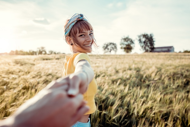 夕暮れ時の麦畑を歩きながら彼氏の手を握って幸せな若い女の肖像。自然の中で旅行を楽しんでいるカップル