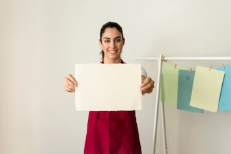 Portrait of a happy young woman holding handmade paper
