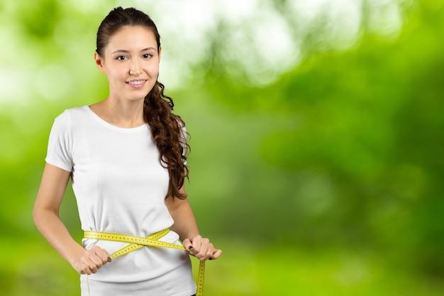 彼女の腰の周りに測定テープを保持している幸せな若い女性の肖像画