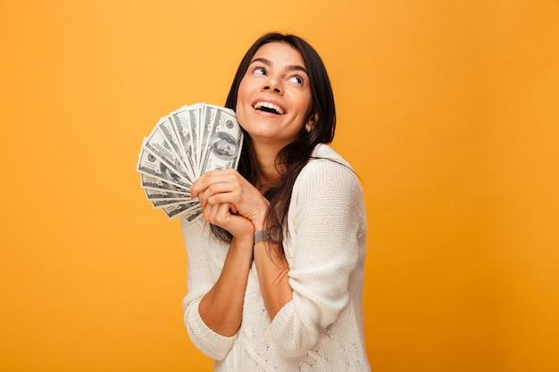 お金紙幣を保持している幸せな若い女の肖像