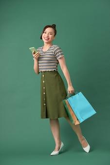 ショッピングバッグと携帯電話を持って幸せな若い女性の肖像画