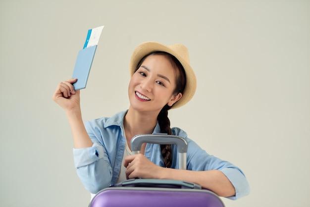 明るい背景で隔離の旅行チケットとパスポートを保持している幸せな若い女性の肖像画