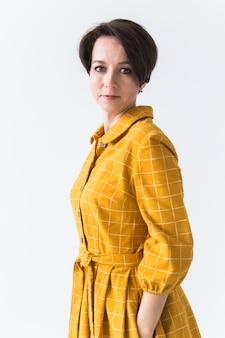 Портрет счастливой молодой женщины в ярко-желтом платье