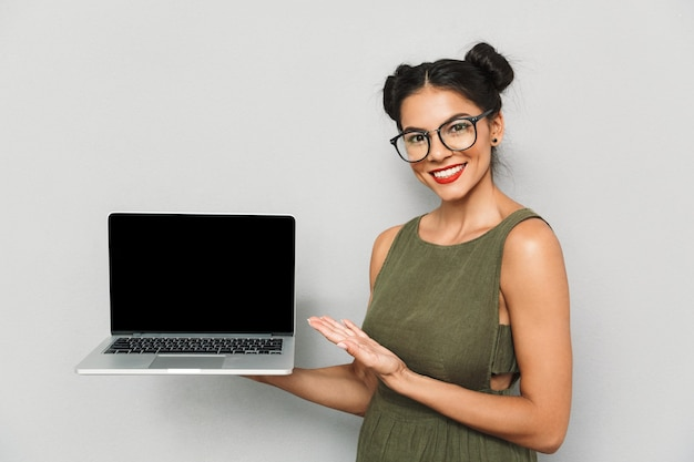 孤立した幸せな若い女性の肖像画、空白の画面のラップトップを表示