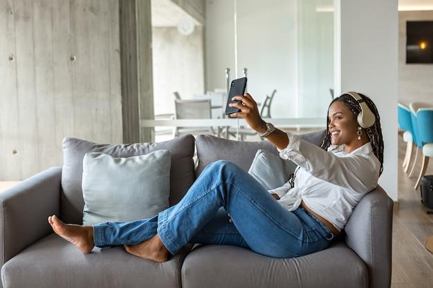 ヘッドフォンで音楽を聴き、自宅のソファに寄りかかって自分撮りをしている幸せな若い女性の肖像画。家の人々の概念。