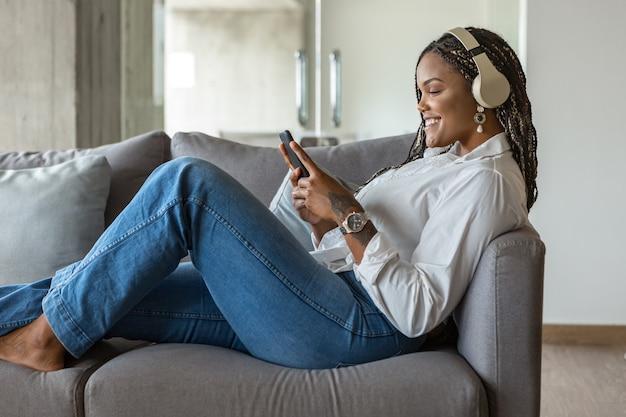 自宅のソファに寄りかかってヘッドフォンで音楽を聴き、携帯電話を使用して幸せな若い女性の肖像画。家の人々の概念。