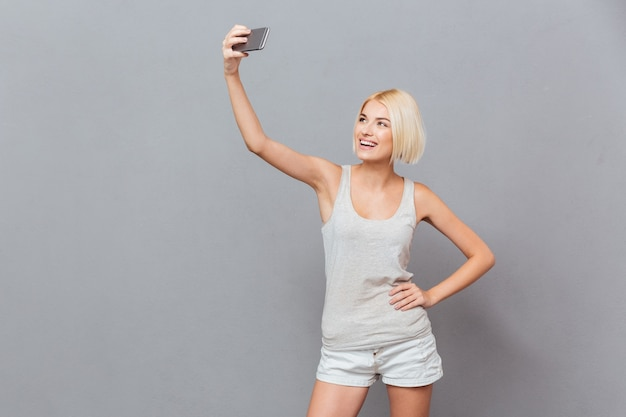 灰色の壁に分離されたスマートフォンでselfie写真を作る幸せな若い女性の肖像画