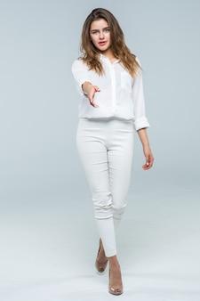 Портрет счастливой молодой женщины, предлагая рукопожатие на белом фоне