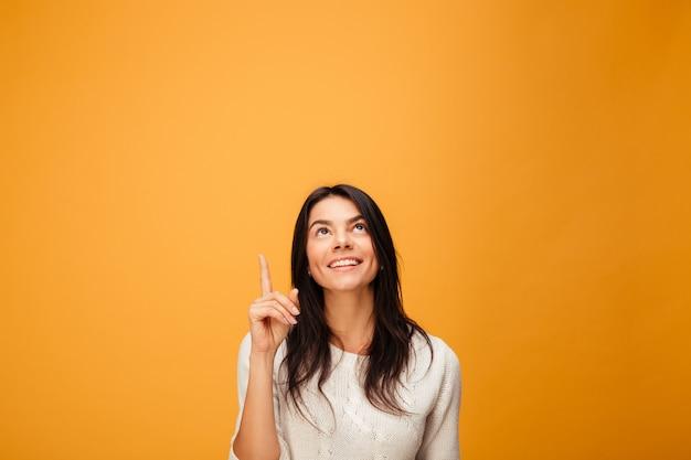 손가락을 가리키는 행복 한 젊은 여자의 초상화