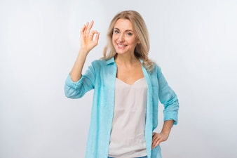 Portrait of a happy young woman showing ok sign against white backdrop