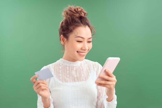Портрет счастливой молодой женщины, показывающей пластиковую кредитную карту при использовании мобильного телефона, изолированного на зеленом фоне