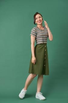 孤立した電話で話している幸せな若い女性の肖像画