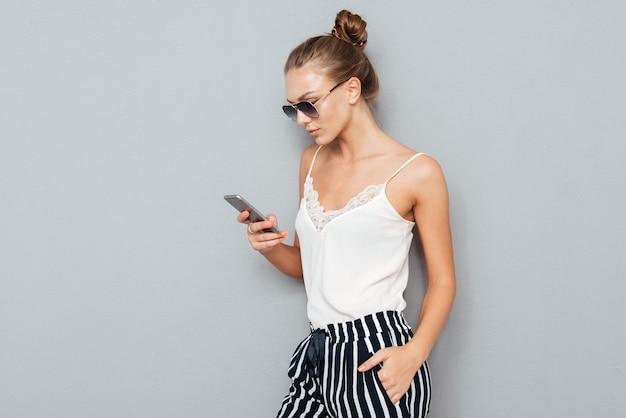Портрет счастливой молодой женщины с помощью смартфона, изолированные на сером фоне