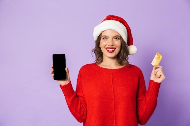 Портрет счастливой молодой женщины в шляпе рождества изолированной над фиолетовой стеной, использующей мобильный телефон держа кредитную карту.