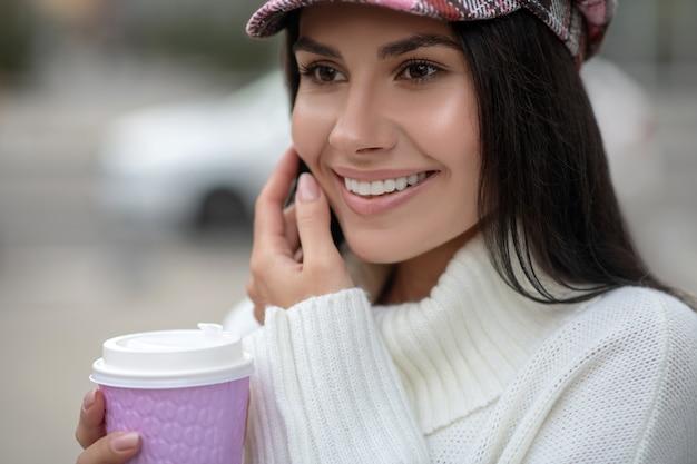 Портрет счастливой молодой женщины, держа чашку с кофе