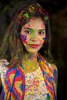Портрет счастливой молодой женщины с ярким лицом по случаю фестиваля красок холи.