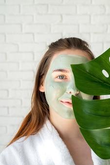 モンステラの葉を保持している顔のマスクを持つ幸せな若い女性の肖像画