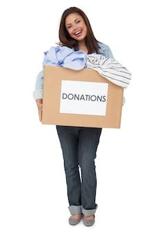 Портрет счастливый молодой женщины с пожертвованием одежды, стоя на белом фоне