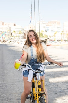Portrait of a happy young woman with glass of juice sitting on bicycle