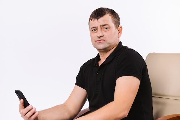 Портрет слабослышащего человека, сидящего в офисном кожаном кресле со смартфоном. белый