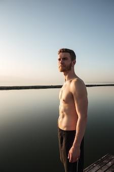 물과 함께 야외 서 건강한 shirtless 스포츠맨의 초상화