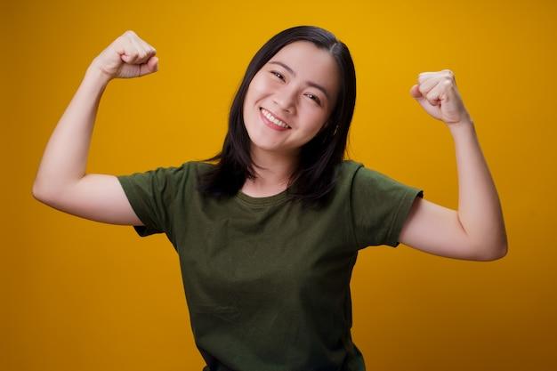 Портрет здоровой женщины, изолированной над желтой стеной.