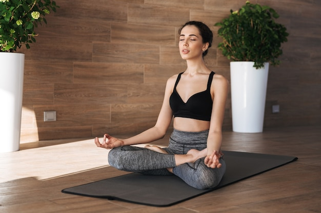 Портрет здоровой молодой спортсменки, делающей упражнения йоги